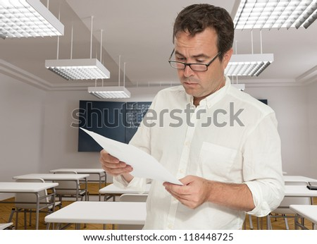 Serious teacher in a classroom, reading a paper