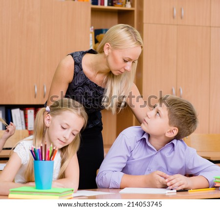 serious teacher talking with a student during the exam - stock photo