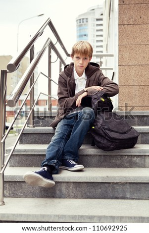 Serious teen sitting on stairs. outdoor - stock photo