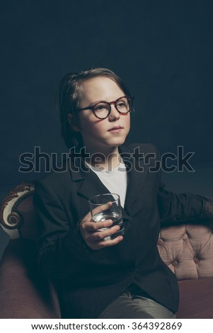 Serious teenage boy in suit with glasses sitting on couch holding glass of water. - stock photo