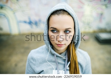Serious teenage girl with hood on listening to music from headphones standing on background of graffiti wall - stock photo