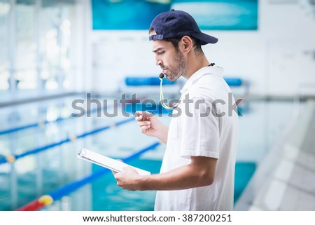 Serious trainer holding clipboard and blowing whistle at the pool - stock photo
