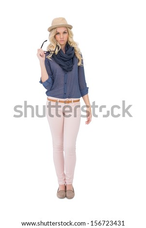 Serious trendy blonde holding her classy glasses on white background - stock photo