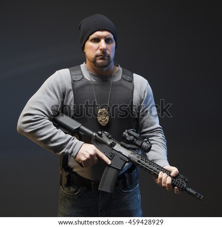 Serious Undercover Law Enforcement Special Agent with rifle. - stock photo