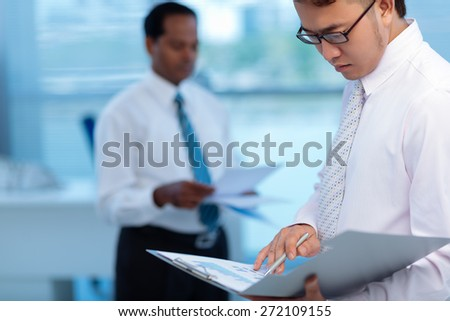 Serious Vietnamese manager looking at document in his hands - stock photo