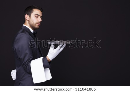 Serious waiter looking to his silver tray against dark background - stock photo