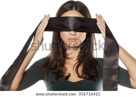 serious woman adjusts blindfold over her eyes - stock photo