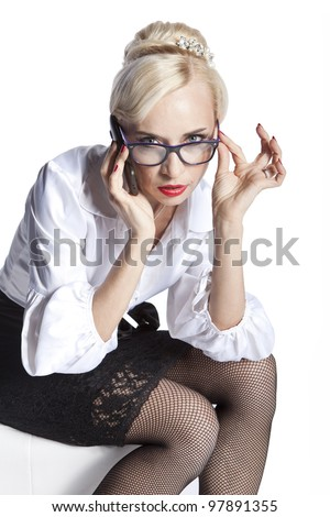 serious woman blonde with the phone and glasses on a white background - stock photo