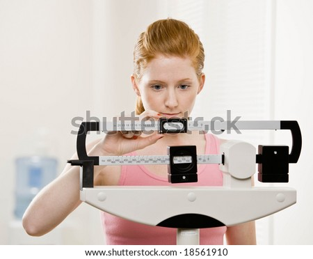 Serious woman checking dieting success by weighing herself on scale - stock photo
