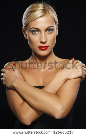 Serious woman crossed her arms, isolated over black background - stock photo