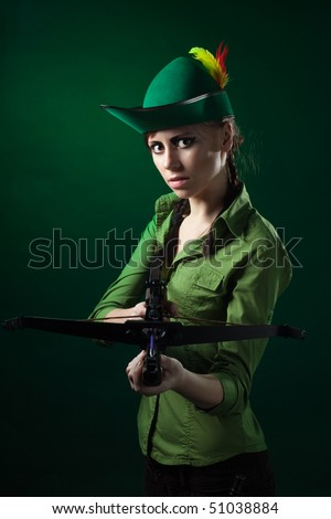 Serious woman frowning holding crossbow and aiming