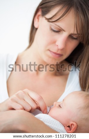 Serious woman giving a pacifier to her daughter against a grey background