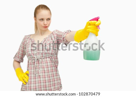 Serious woman holding a spray bottle while looking away against white background - stock photo