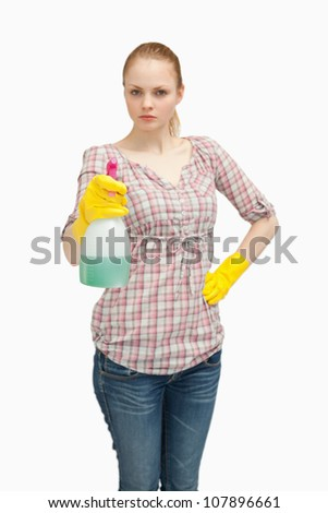 Serious woman holding a spray bottle while standing against white background - stock photo