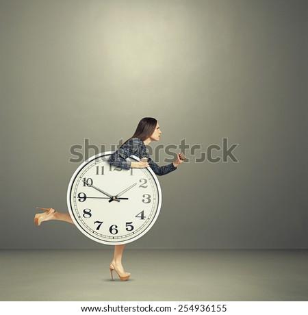 serious woman holding big clock and running forward - stock photo