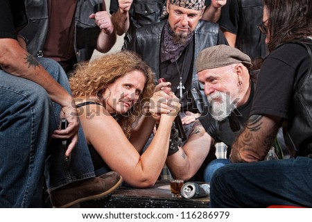 Serious woman in arm wrestling contest with biker gang