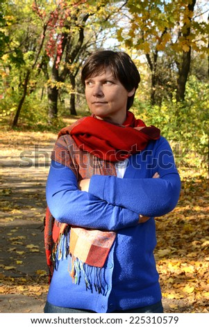 Serious woman in autumn park - stock photo