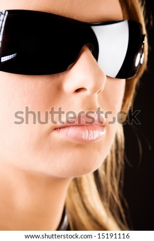 Serious woman in sunglasses portrait. On dark background. - stock photo