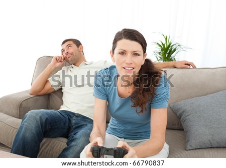 Serious woman playing video game while her boyfriend waiting for her on the sofa at home - stock photo