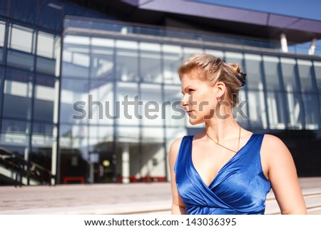 Serious woman portait on business building background. - stock photo