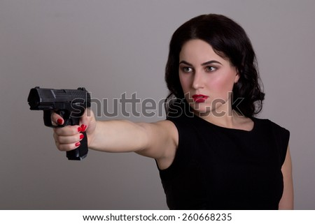 serious woman shooting with gun isolated on grey background - stock photo