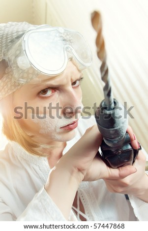 Serious woman with goggles on her forehead holding hand drill - stock photo