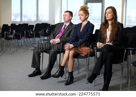 Serious women and man sitting in row at conference - stock photo
