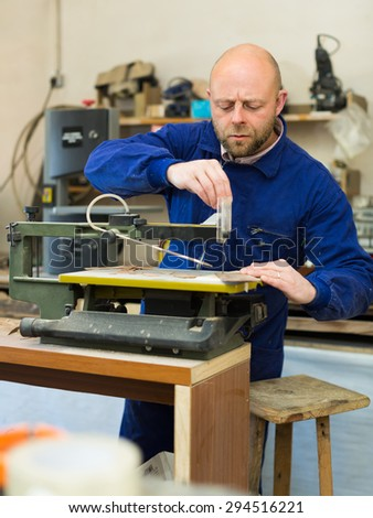Serious woodworker working on a machine at wood workshop - stock photo
