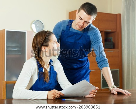Serious workers in uniform reading financial documents at table
