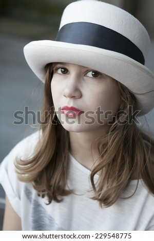 serious youn girl in tall hat - stock photo