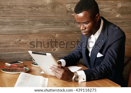 Serious young African American businessman holding digital tablet, looking at the screen with concentrated expression while filling in some papers, sitting at a cafe, having coffee during lunch break - stock photo