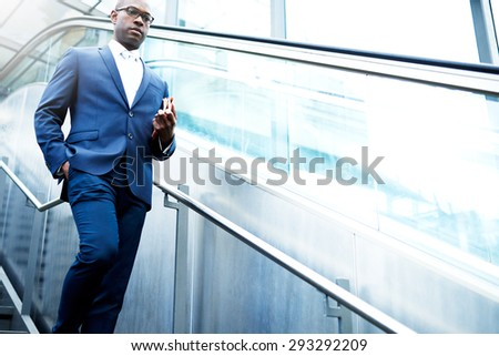 Serious Young African American Businessman with Newspaper Using Stairs in Going Down Inside the Building. - stock photo