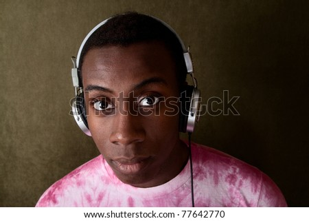 Serious young African-American in pink tie-dye and headphones - stock photo