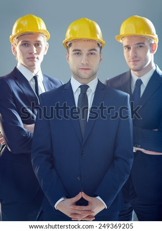 Serious young architects in suits and helmets looking at camera - stock photo