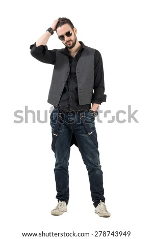 Serious young bearded man running fingers through hair looking at camera. Full body length portrait isolated over white background.