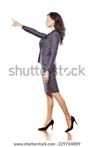 serious young beautiful business woman pointing at blank - stock photo