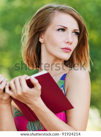 serious young beautiful short-haired woman holding red book looking sideways background summer green park