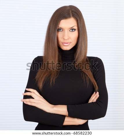 serious young beautiful woman with crossed arms - stock photo