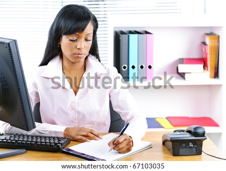 Serious young black business woman writing at desk in office - stock photo