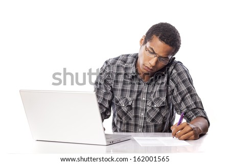 Serious young black man writes data from his laptop and talking on the phone - stock photo