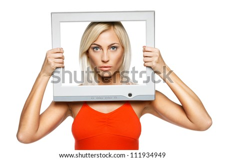 Serious young blond female looking through the TV / computer screen frame, over gray background