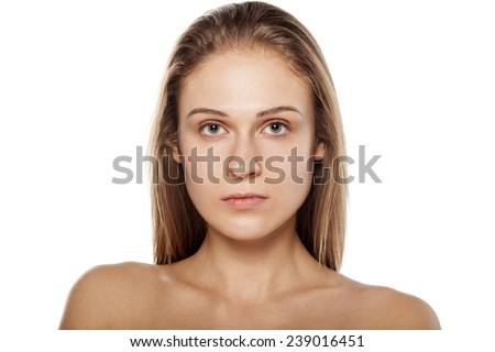 serious young blond woman posing on a white background - stock photo