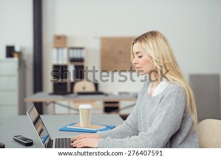 Serious Young Blond Woman Typing Something on her Laptop Computer at her Table Inside the Office. - stock photo