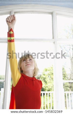 Serious young boy in superhero costume with raised fist looking up - stock photo