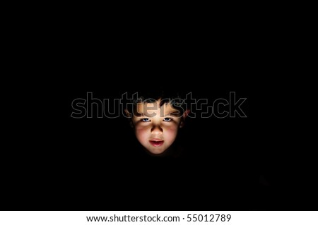serious young boy looking from darkness - stock photo