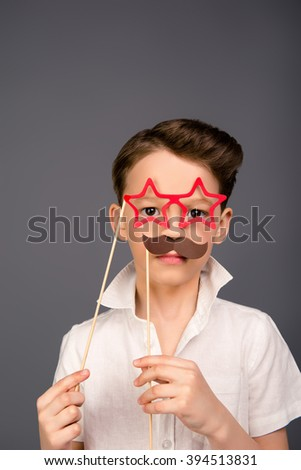 Serious young boy posing with paper mustache and glasses like stars