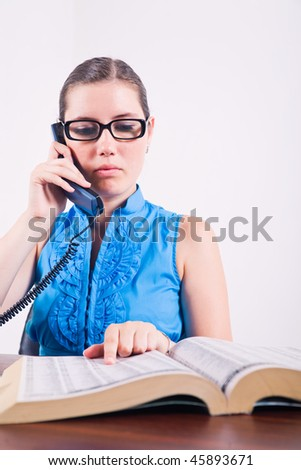 Serious young brunette business woman on the phone with open phone book.