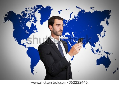 Serious young business man looking at his smartphone, on world map background. - stock photo