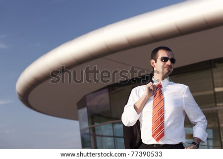 Serious young business person in white shirt, orange tie and sunglasses standing in front of office building with blue sky in background. - stock photo