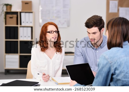 Serious Young Business Professionals Discussing Project Plans at the Table Inside the Office - stock photo